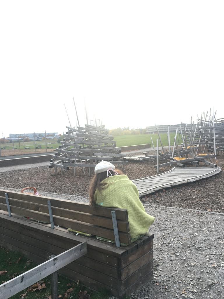 Ein Mädchen sitzt mit einer Decke um die Schultern mit dem Rücken zum Betrachter auf einer Bank. Vor ihr ein Spielplatz