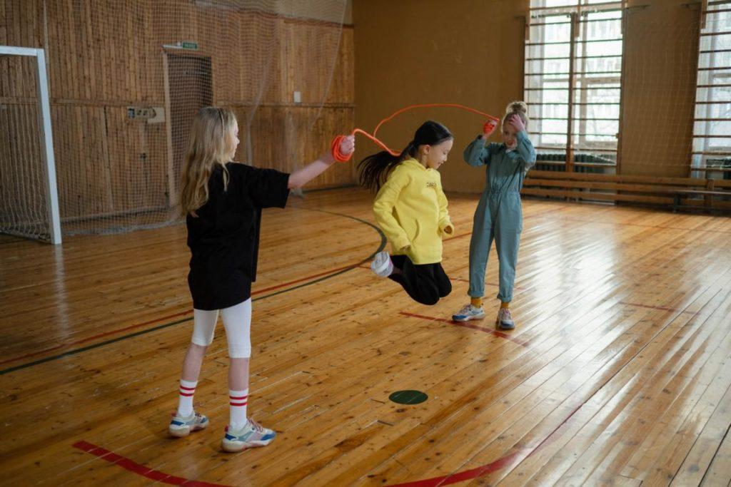 Drei Kinder springen Seil in einer Turnhalle. Das Bild soll zeigen, dass das Spaß macht. Jedenfalls wenn man nicht dafür benotet wird.