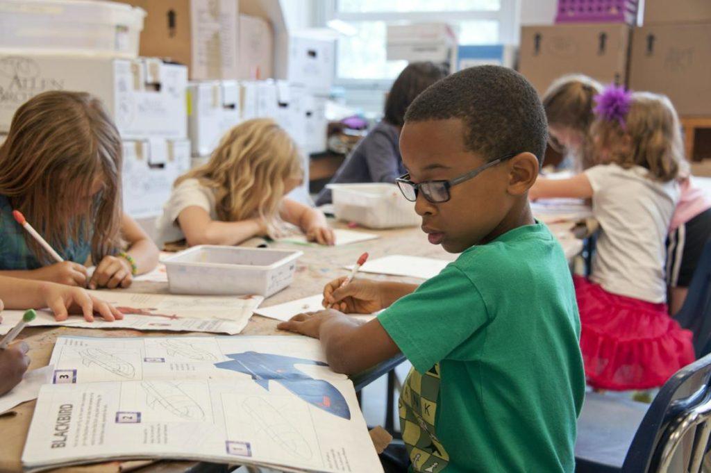 Ein etwa achtjähriger dunkelhäutiger Junge mit Brille blickt im Vordergrund auf eine Zeitschrift. Er hält einen Stift in der Hand und ist im Begriff, etwas aus der Zeitschrift abzuschreiben. Im Hintergrund sind weitere Grundschulkinder erkennbar.