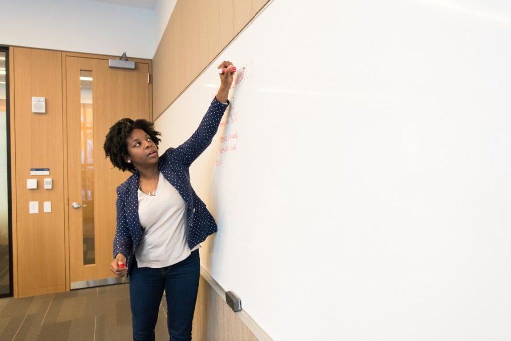 Eine Lehrerin schreibt etwas an ein whiteboard.