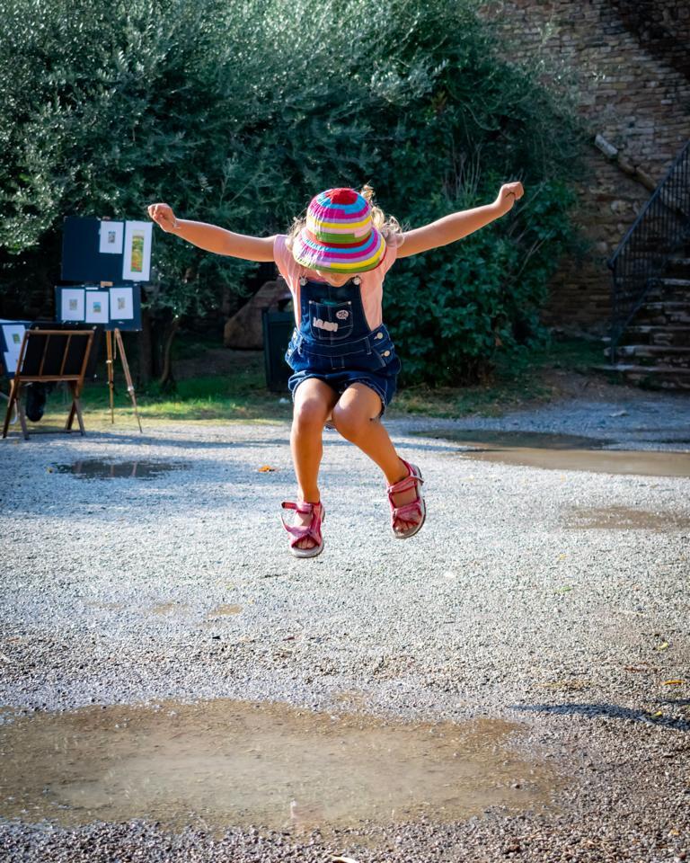 Ein Kind im Sprung über einer Pfütze. Das Bild zeigt, ein sprunghaftes Kind im übertragenen Sinn.