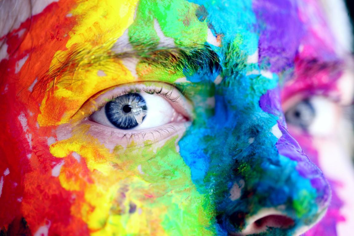 Ein Gesicht mit allen Regenbogenfarben angemalt: Es steht für viele Interessen und Ideen in einer Person.