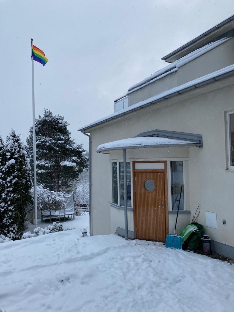 Es ist der Eingang eines Hauses zu sehen. Die Haustür hat ein Bullauge und es liegt Schnee davor. Im Hintergrund ist ein Garten mit einem Trampolin zu erkennen. Das Bild zeigt das Haus, mit dem die hier interviewte Teenagerin sehr zufrieden ist.