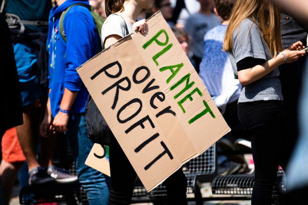 """""""Planet over profit"""" steht auf einem Pappschild, das eine Demo-Teilnehmerin hält. Wahrscheinlich fridays for future-Demo."""
