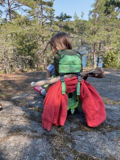 Kind sitzt auf einem Felsen der Halbinsel Björnö im Stockholmer Schärengarten und schaut durch Bäume aufs Wasser.