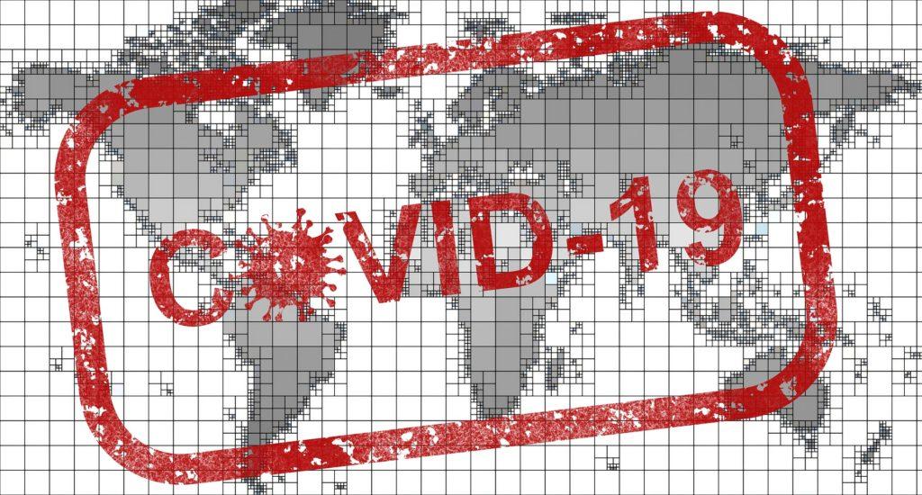 Weltkarte mit einem roten Covid19-Stempel darüber.