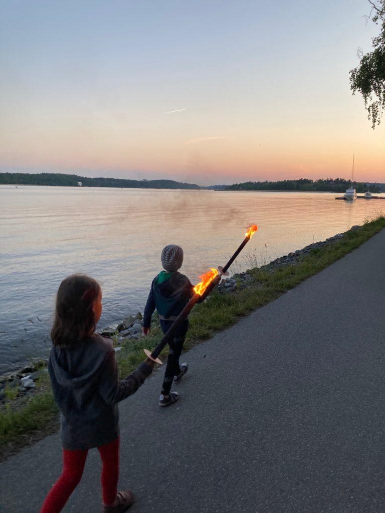 Zwei Kinder mit Fackeln gehen am Meer auf einem asphaltierten Weg spazieren.